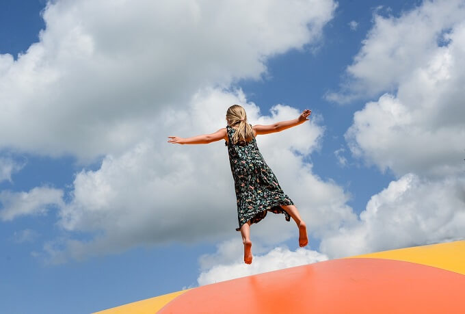 girl in summer dress jumps on trampoline