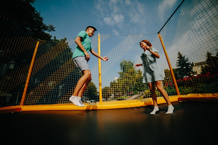Teen boy and girl jumping on outdoor trampoline