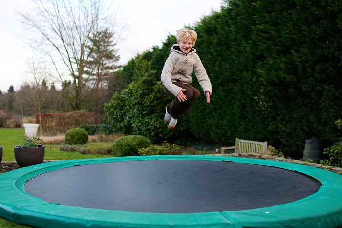 Happy boy jumping on round trampoline