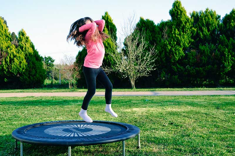 girl jumping on small trampoline
