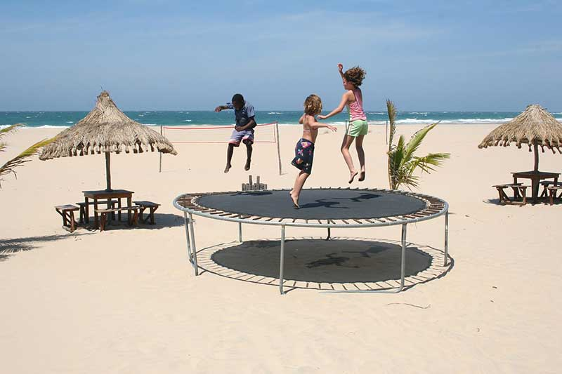 kids playing trampoline in the beach
