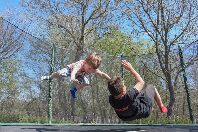 two boys playing on a trampoline