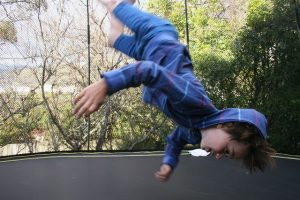 a boy flipping on a trampoline