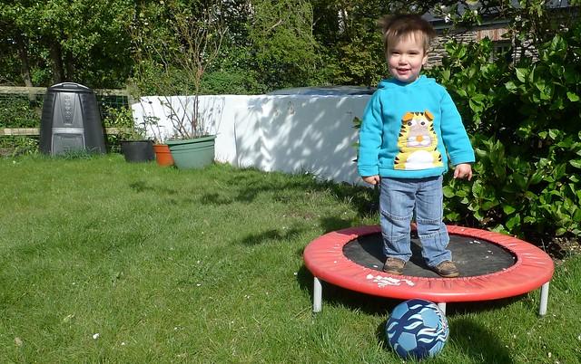 kid boy standing in a mini trampoline