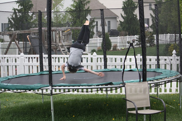 kid jumping on a trampoline playing