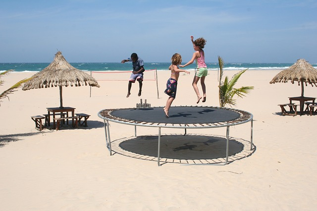 young children playing on a trampoline at a beach