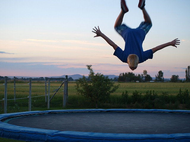 young boy doing a trampoline flip trick